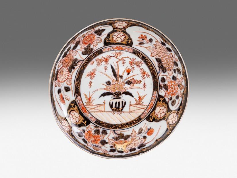 Imari tál. Porcelán. Öblében máz alatti kékkel, máz felett vörössel és arannyal festett krizantémok és hortenziák ábrázolása. Hátoldalán papíretiketten az Eszterháza-kastély leltári jelzésével. Japán, Arita, 1690-1730 között. Átmérő: 27,8 cm.