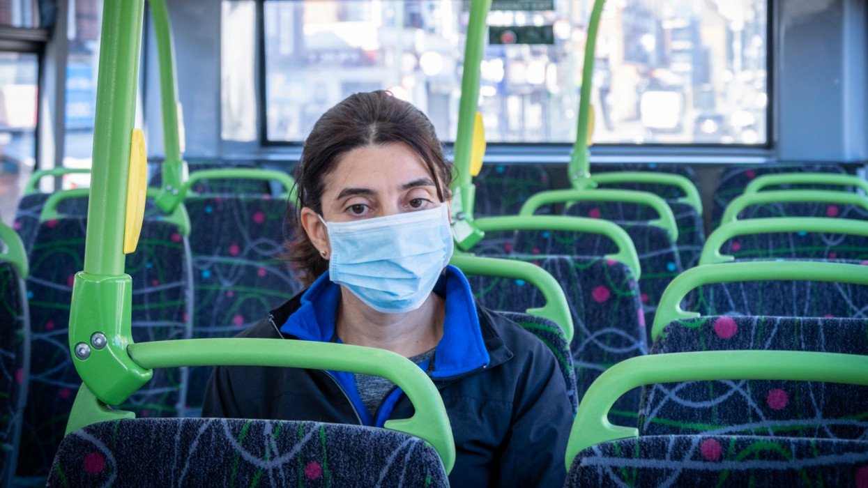 A commuter on her way to work using a face mask on a double-decker bus, during a health lockdown