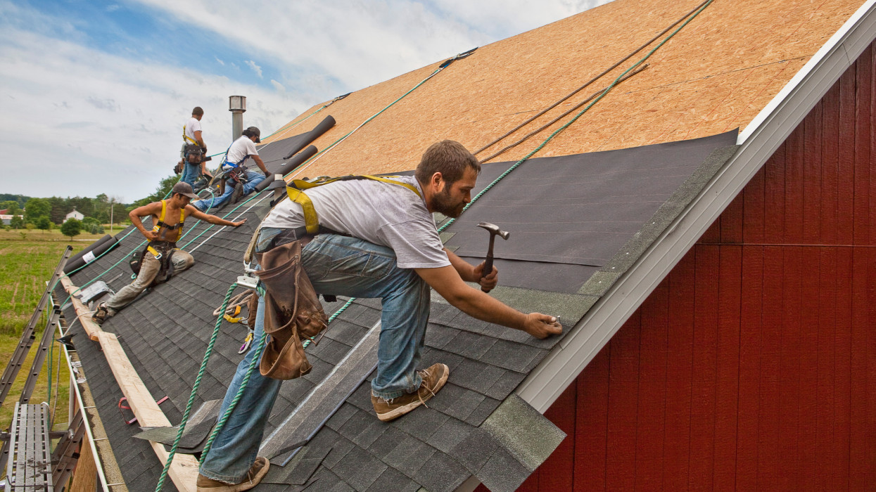 A team of men install watreproofing material and shingles to create a new roof on a rural building.