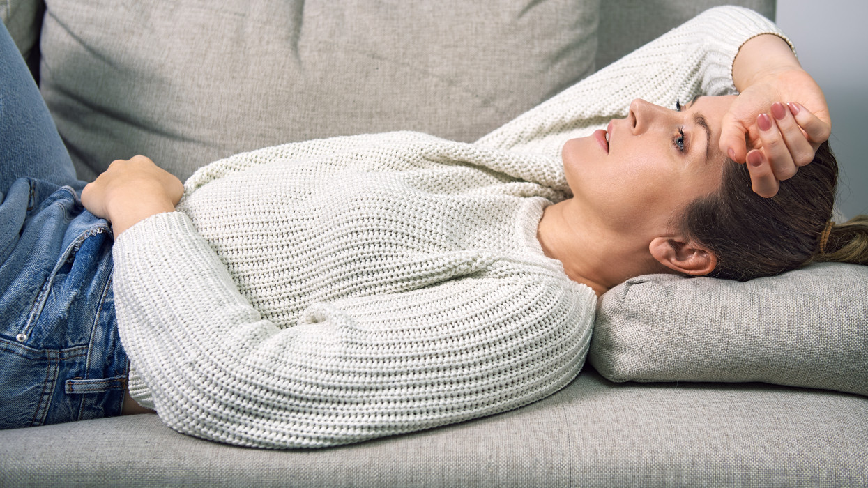A woman lies on a sofa at home and hugs her stomach with her hands. A woman has a stomach ache.