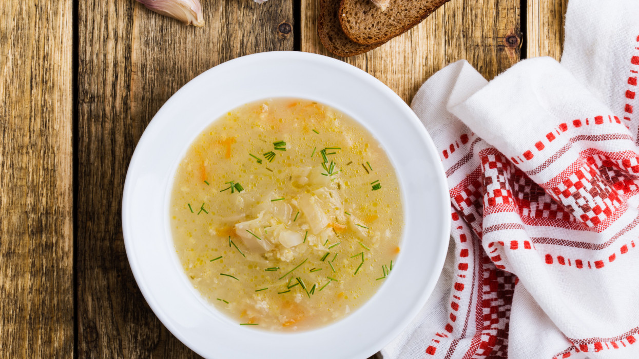 Kapusniak, traditional Ukrainian sauerkraut soup  in white plate on rural table viewed from above, comfort winter food