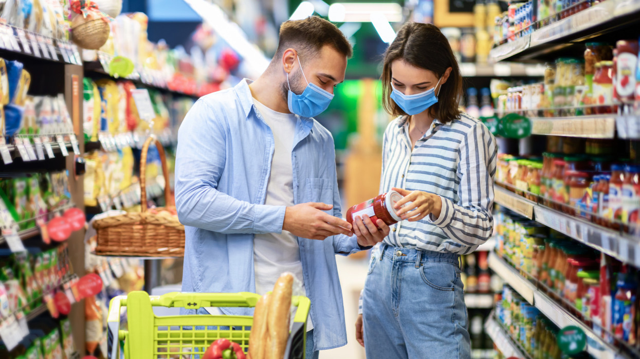 Shopping Together Is Fun. Young smiling couple wearing disposable face masks standing in supermarket mall with trolley cart full of vegetables, buying food and groceries, looking for healthy products