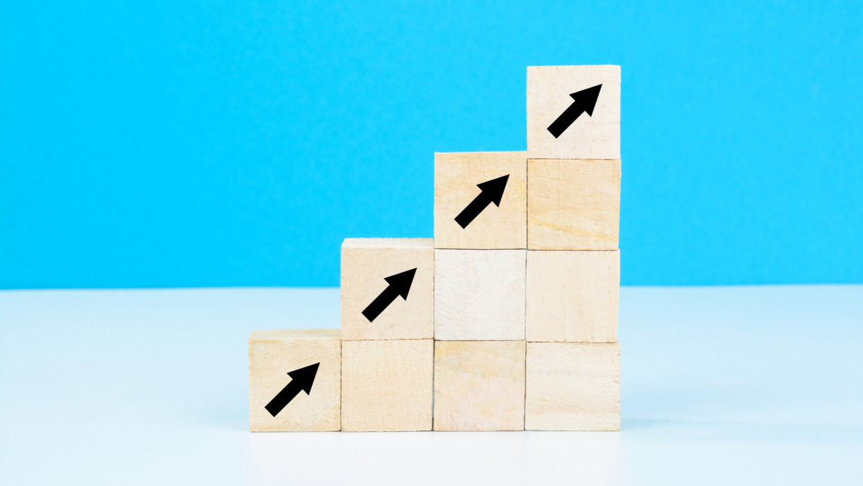 Upward trend. Arrows moving up sign on stacked wooden blocks.