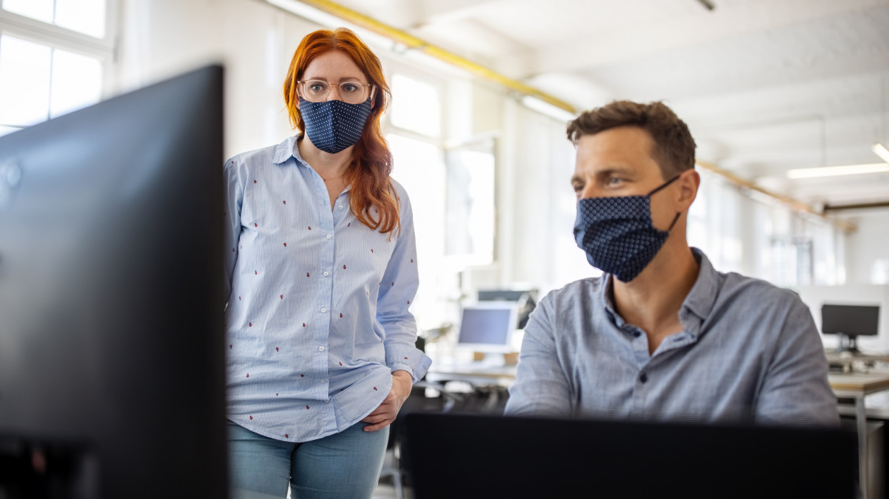 Businessman working on a computer with a female colleague standing by in the office. Business colleagues wearing face masks working together on a computer.