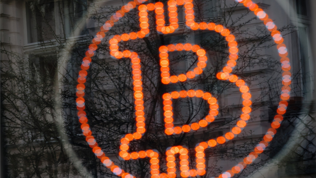A bitcoin LED sign diplayed in a shop window offers service.