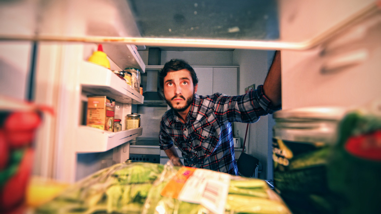 Man looking in refrigerator to find something.