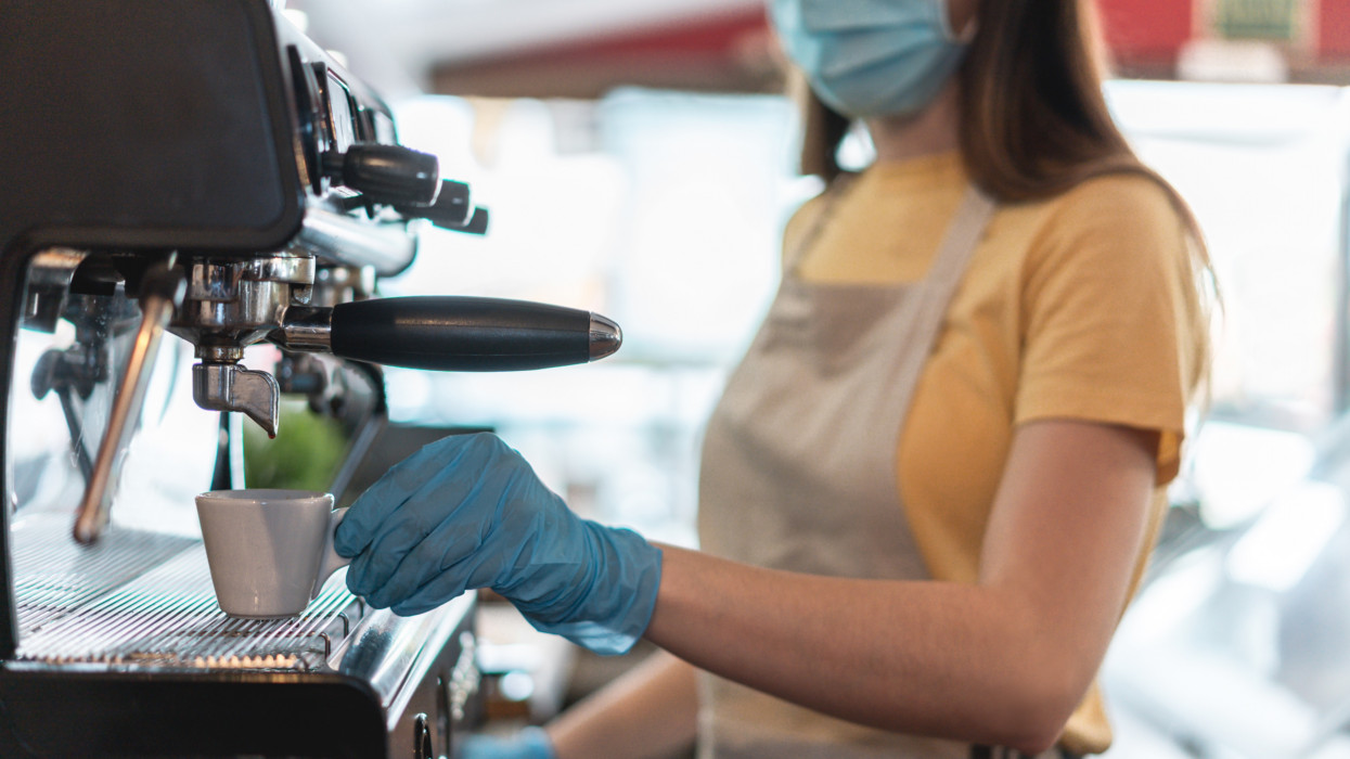Young woman working inside bar restaurant while making coffee wearing gloves and face mask for coronavirus spread prevention - Protective measures at work during Covid-19 outbreak - Soft focus on cup