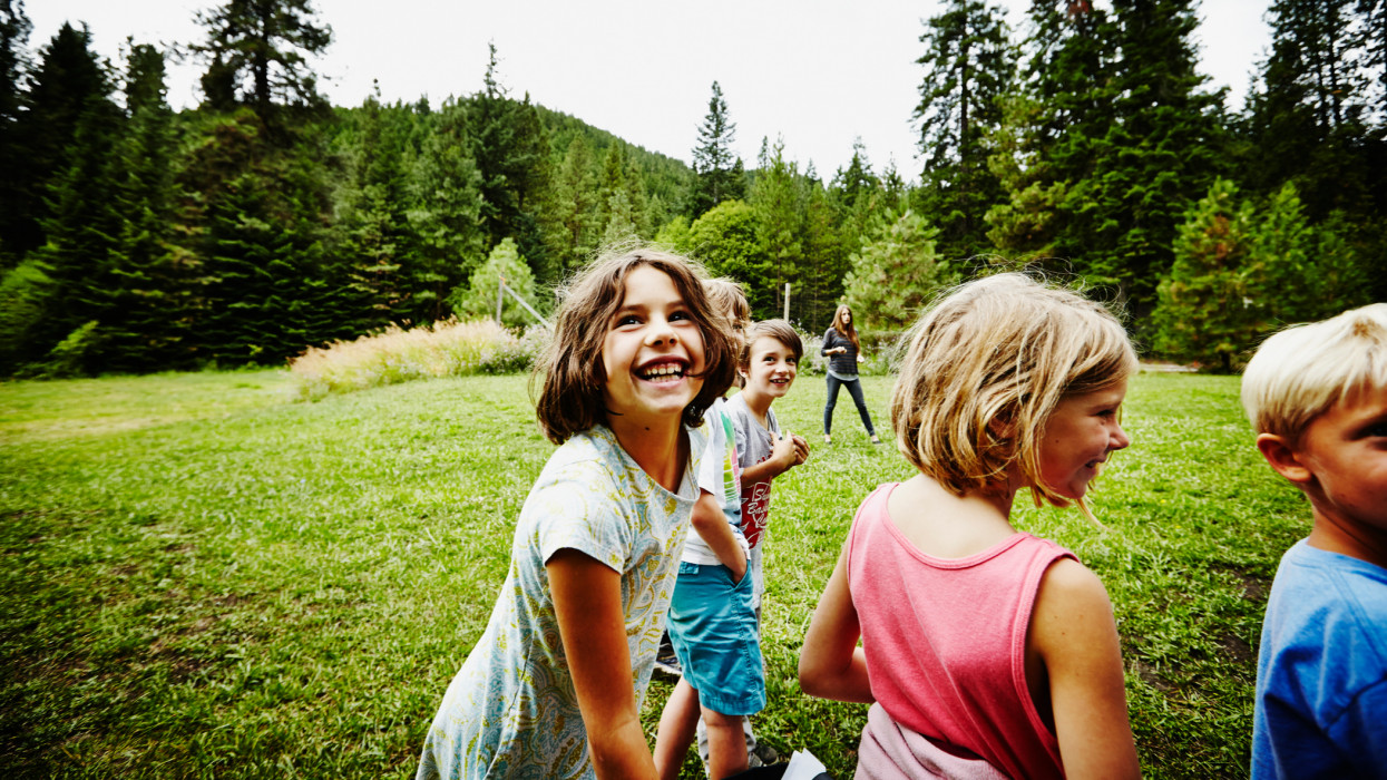 Group of laughing young kids standing in line starting running race in grass field at summer camp