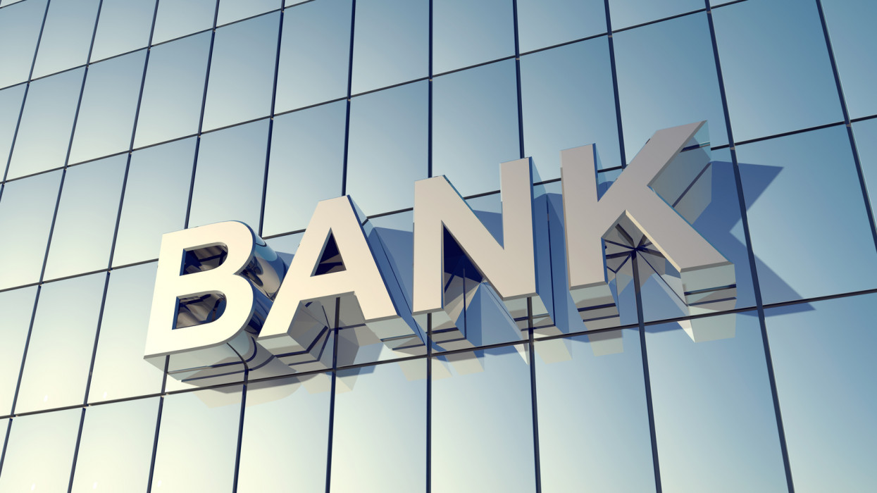Glass front of a bank building with the word BANK on the Building