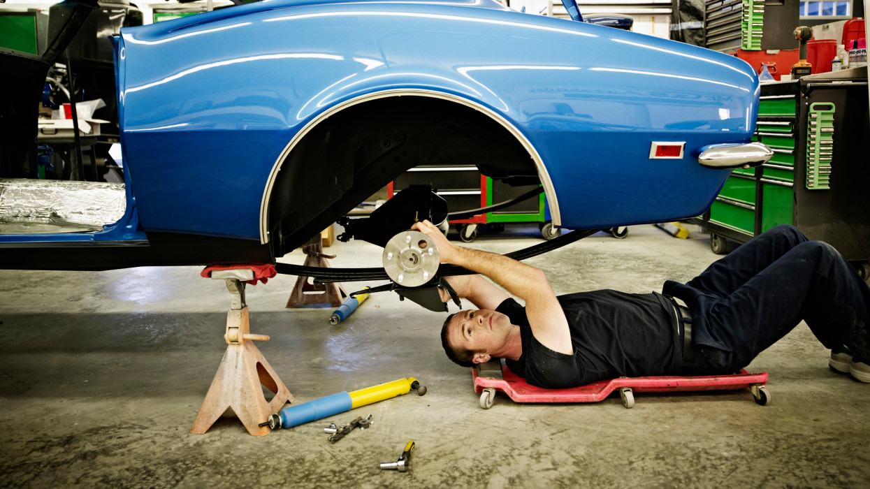 Mechanic lying on floor in garage working on rear axle of classic car being restored