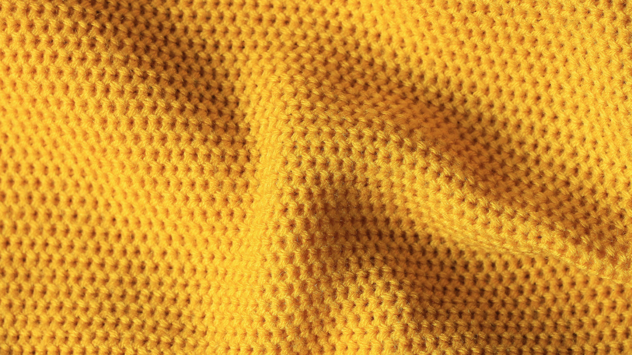 Texture of knitted fabric of yellow color. Bright yellow background. Fabric mustard color.