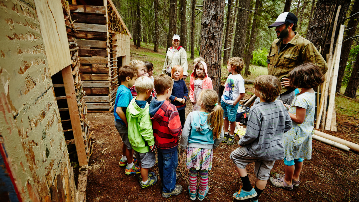 Camp counselor giving instructions to group of young kids standing in circle in front of wooden forts in woods at summer camp
