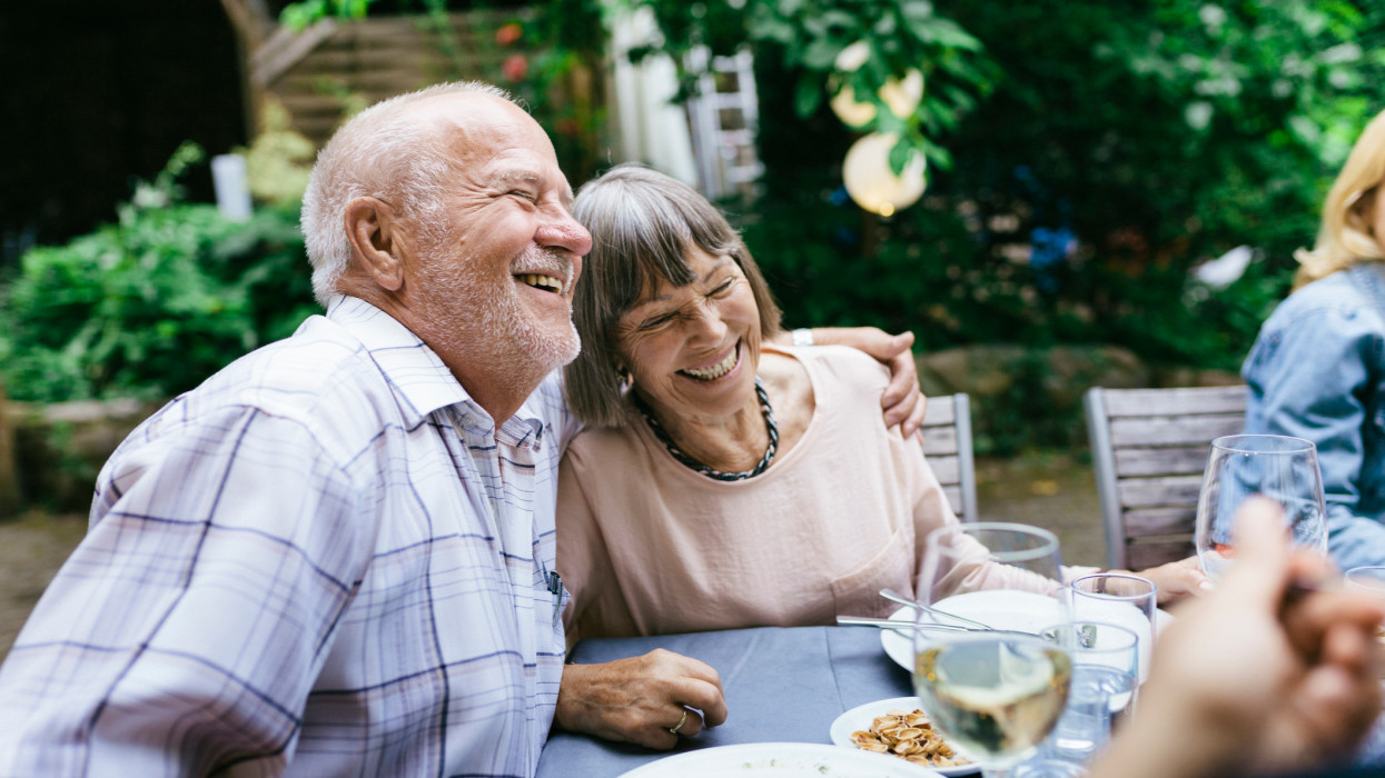 An elderly couple embracing, enjoying an outdoor meal with the family in a courtyard.