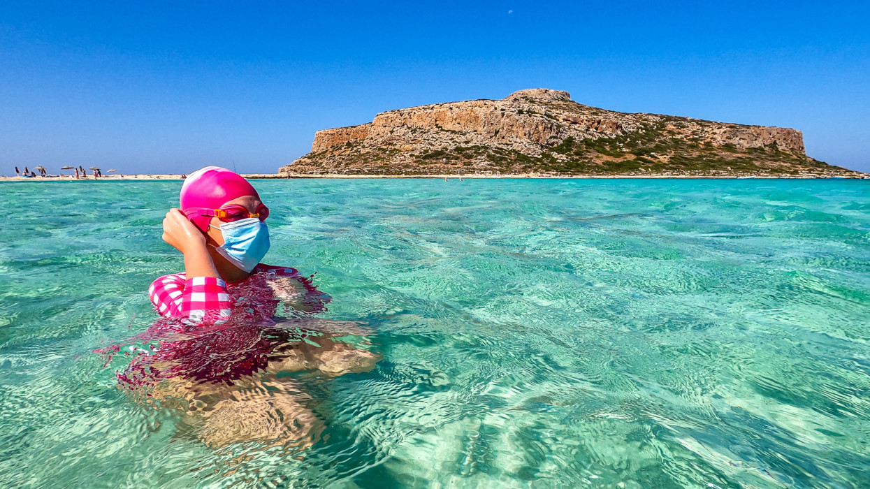 Girl puting a face protection mask while she is in sea at the most beautiful beach in Crete, Balos beach. Greece
