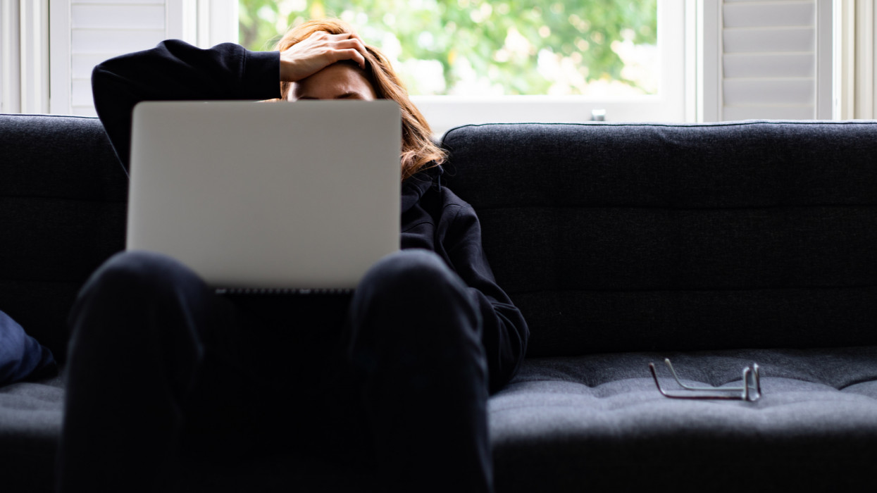 A woman sitting on a sofa, feeling depressed, looking for a job.Reading bad news.