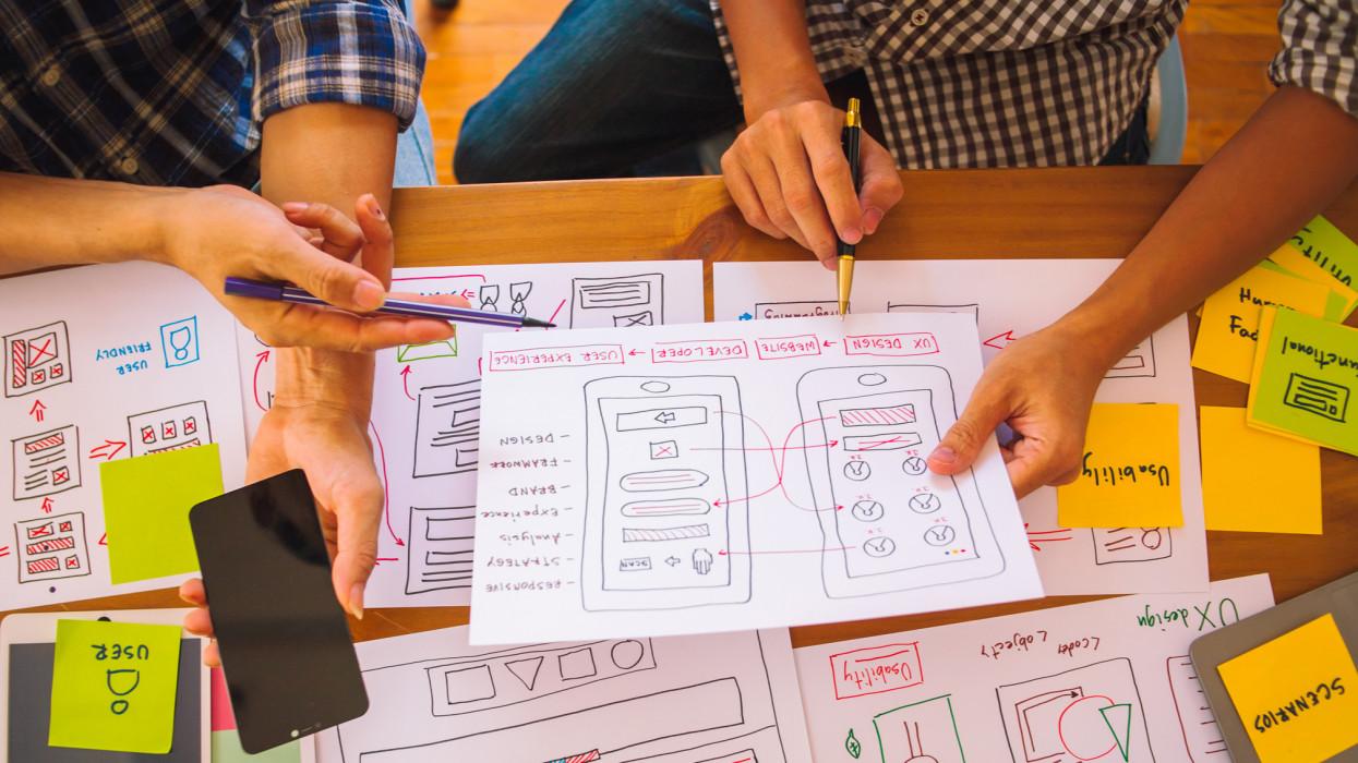 The web designer team is helping to design applications for mobile phones. UX UI designer concept