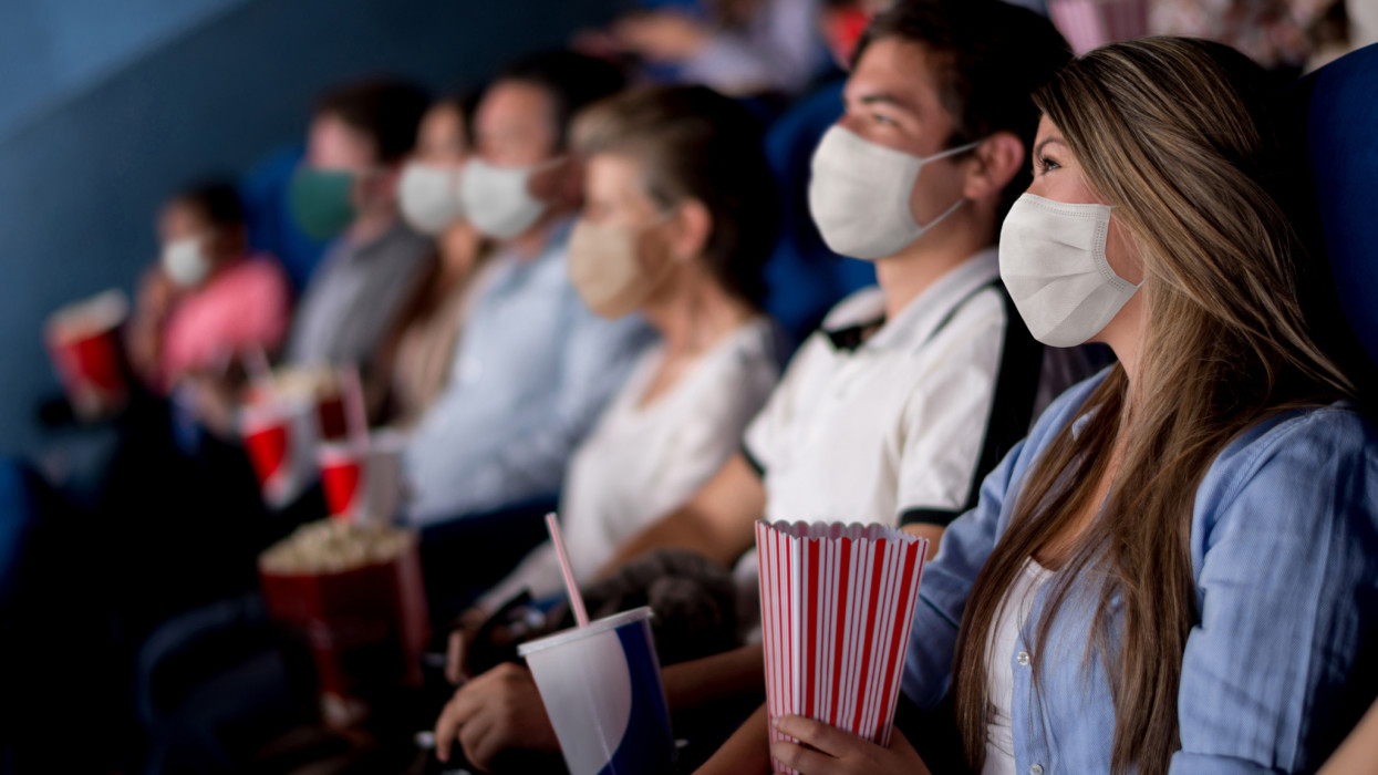 Group of people at the cinema wearing facemasks while watching a movie - reopening of businesses
