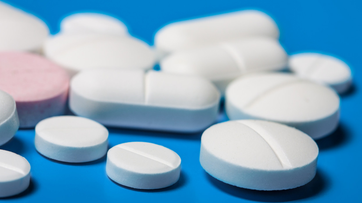 Pills close-up on a blue background. Variety of tablets close-up. Bright blue background