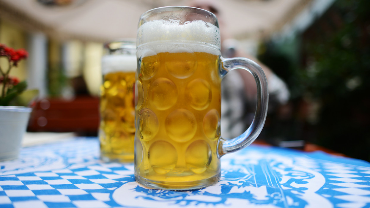 Two large mugs each containing a liter of octoberfest beer. Standing on a restaurant table with a classic Bavarian blue and white table cloth.
