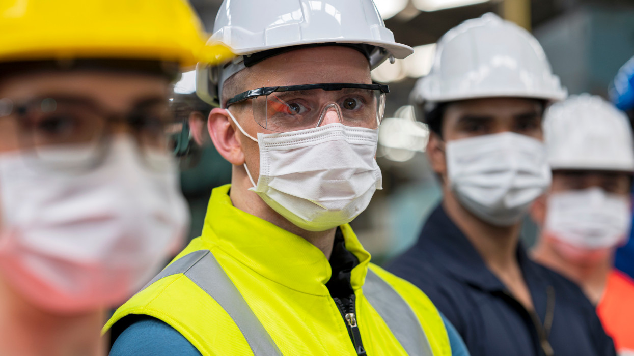 Shot of Business owner smiling under protective face mask while standing side by side with working team in a heavy industry.