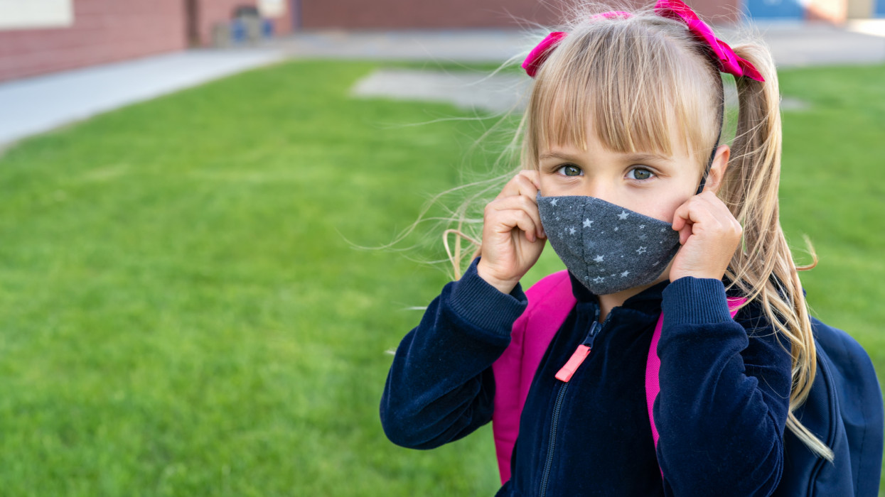 Young student caucasian girl looking at camera and wear protective face mask before school day. Ready for new school year with pandemic restrictions. School reopen. Return back to school. Copy space.