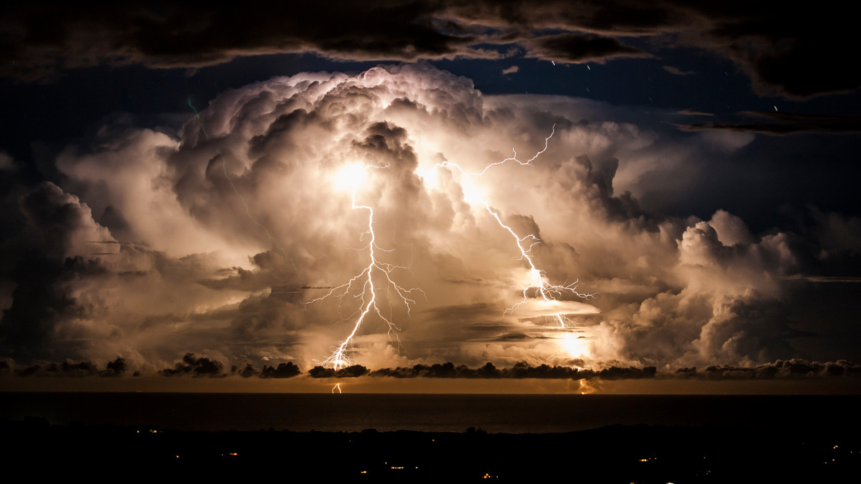 Storm clouds shroud an electrical storm of the coast of  Byron Bay at night. Taken from the hinterland around Mullumbimby, early evening in Autumn as the changing sky dazzles with a natural light show of lightning bolts and billowing clouds dance in the sky for hours.