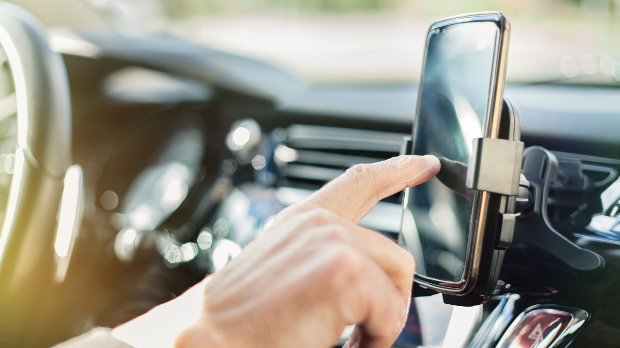 Close up of a man using smart phone while driving