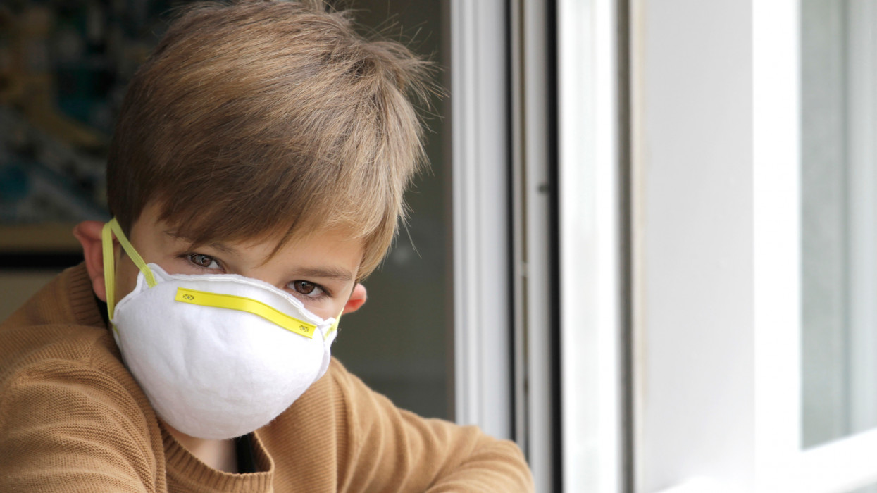 Boy with face mask looking out of window. Coronavirus Quarantine Concept