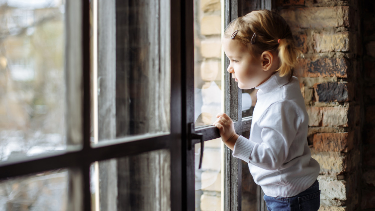 Sad child looking out the window.