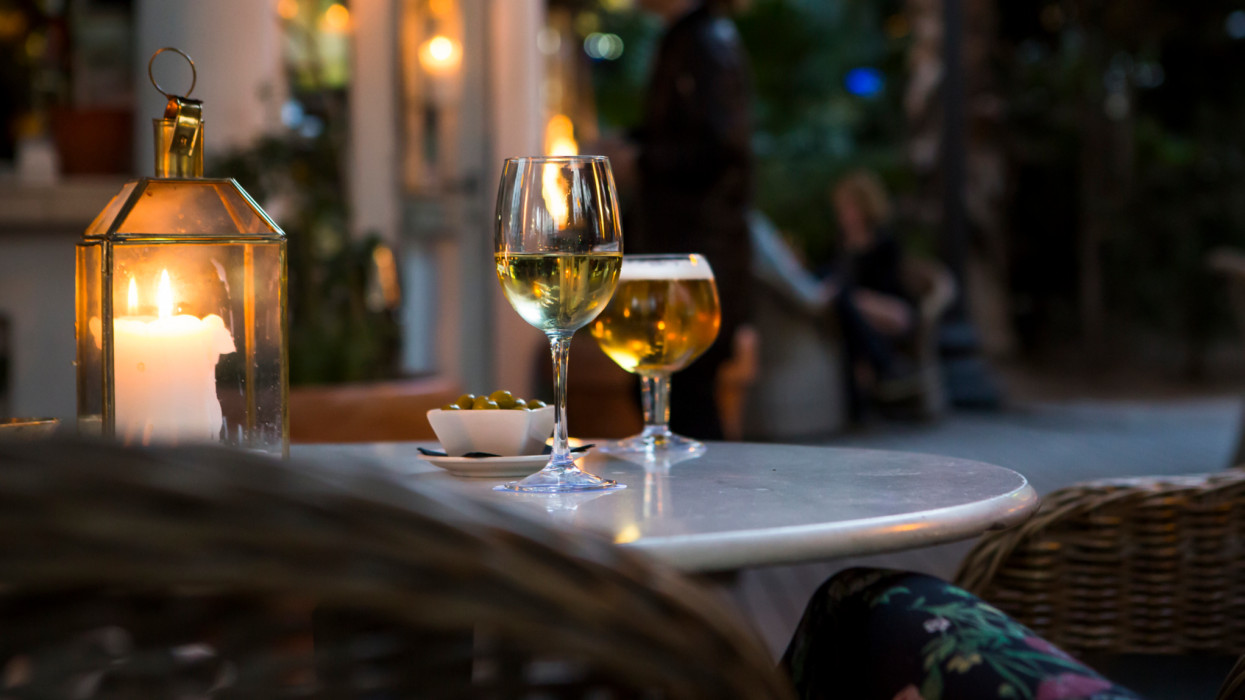 A glass of wine and beer with olives on a table at a cozy restaurant.