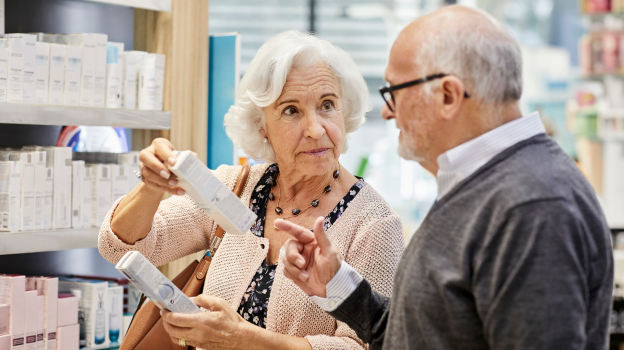 Elderly woman discussing over medicine with man at store. Senior couple is buying merchandise. They are wearing sweaters in pharmacy.