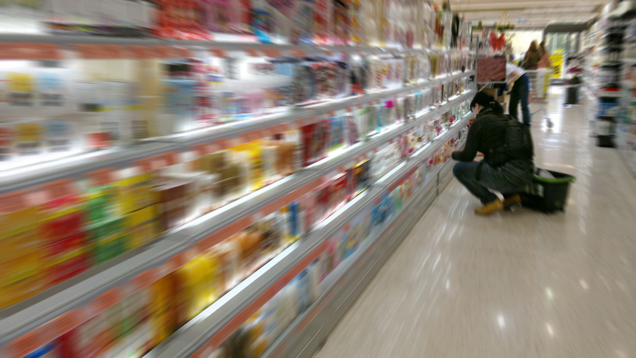 In Supermarket looking a woman at colorful goods. Blurred.