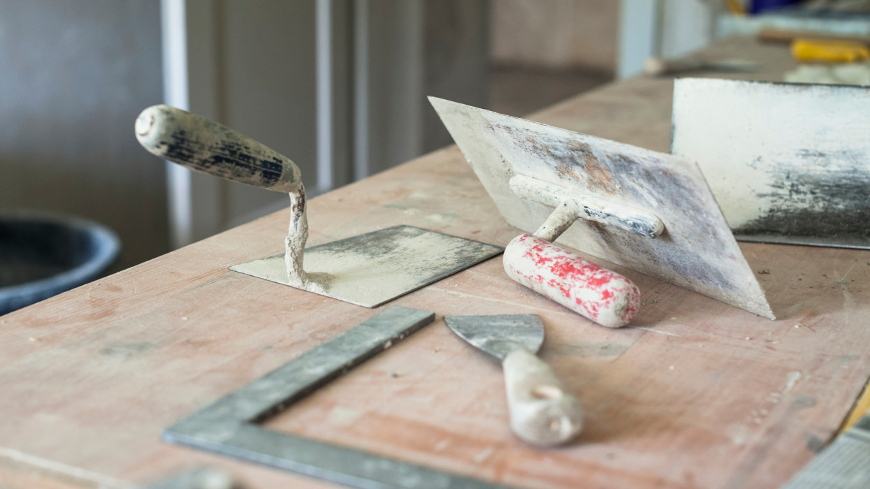 Tools of a plasterer/mason on a table located at a construction site