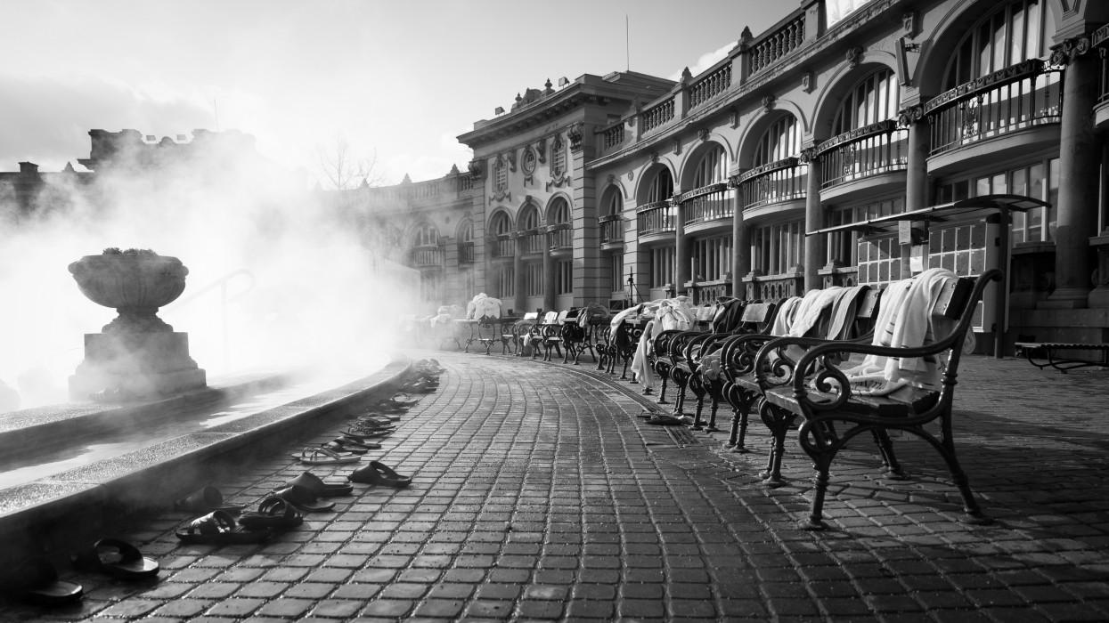 Les bains chauds Szechenyi à Budapest. Image en noir et blanc montrant les vapeurs de la piscine principale des bains, des bancs ou se trouvent des serviettes des baigneurs.