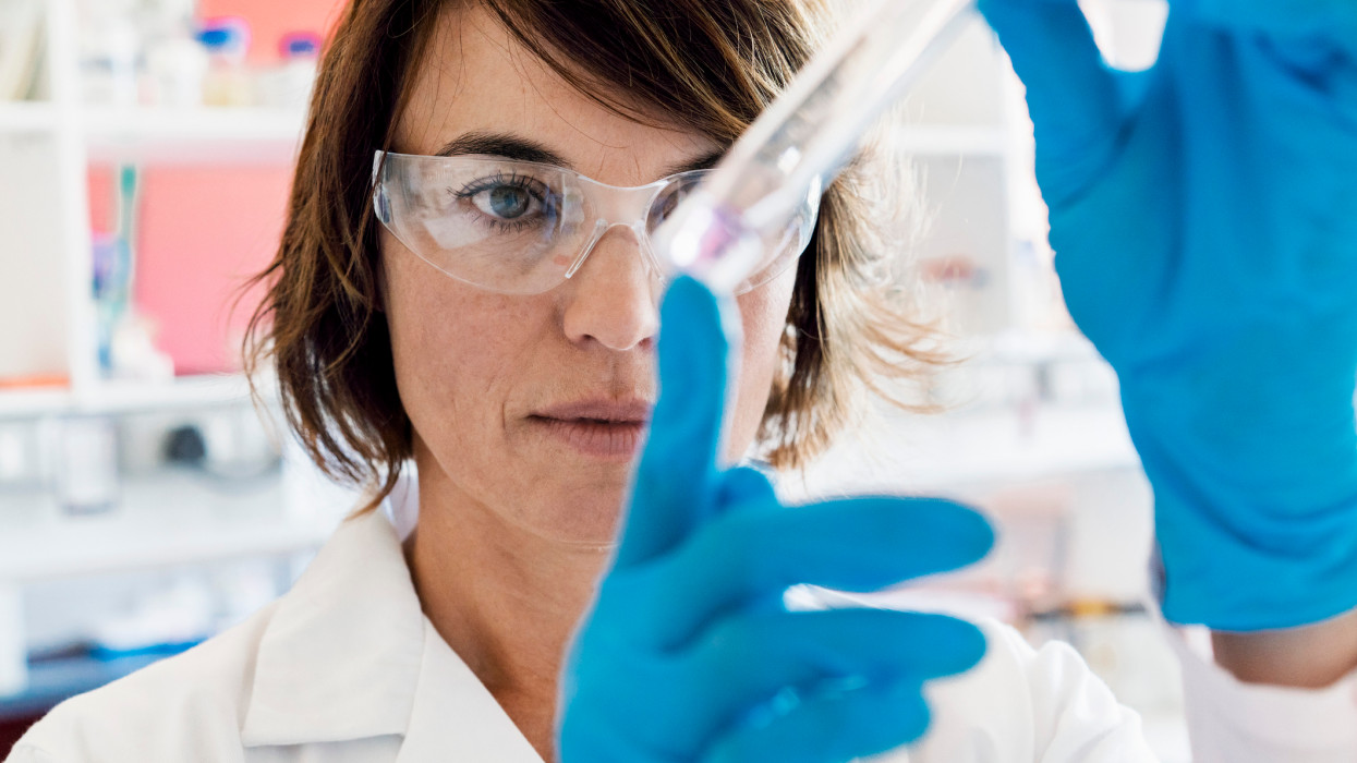 A photo of serious chemist analyzing chemical in test tube. Concentrated female scientist wearing protective eyeglasses and lab coat. She is working in laboratory.
