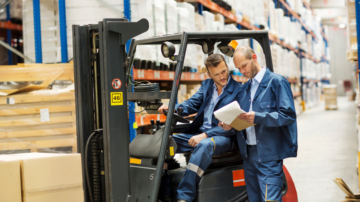 Workers discussing over documents while using forklift at warehouse