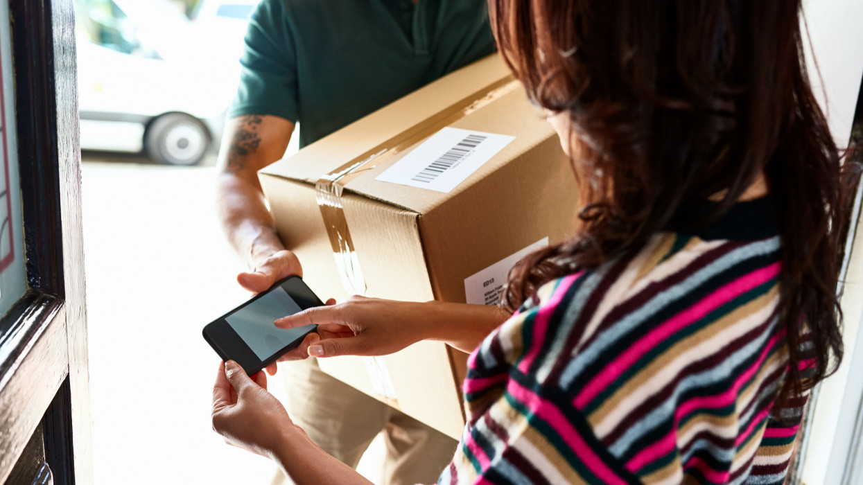 Female customer at front door holding smartphone and receiving package from delivery man, service, identity, online shopping