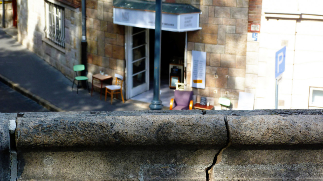 deteriorating gray textured cracked stone balustrade. blurred cafe patio in the background. selective focus. blurred aerial view of street terrace. tables and colorful chairs. retro style street lamp