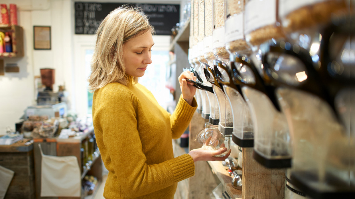 A woman dispenses oats into a jar in a zero waste whole foods store.