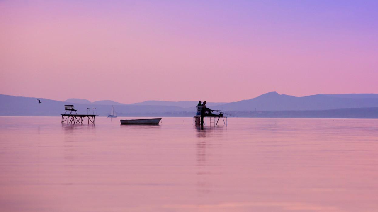 People fish on platforms during sunset at Lake Balaton.