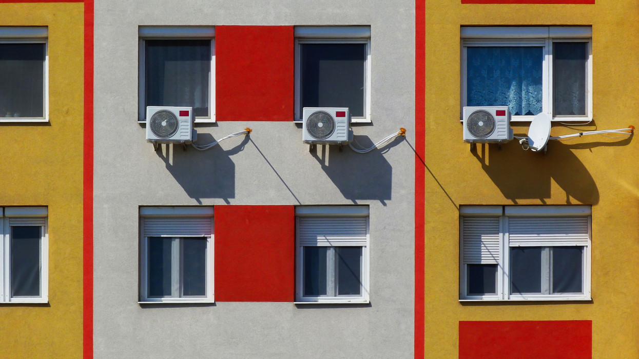 air conditioning wall installed condenser units. residential windows on condominium building exterior wall or facade. closeup detail. colorful newly re insulated textured stucco finish. comfort and home ownership concept.