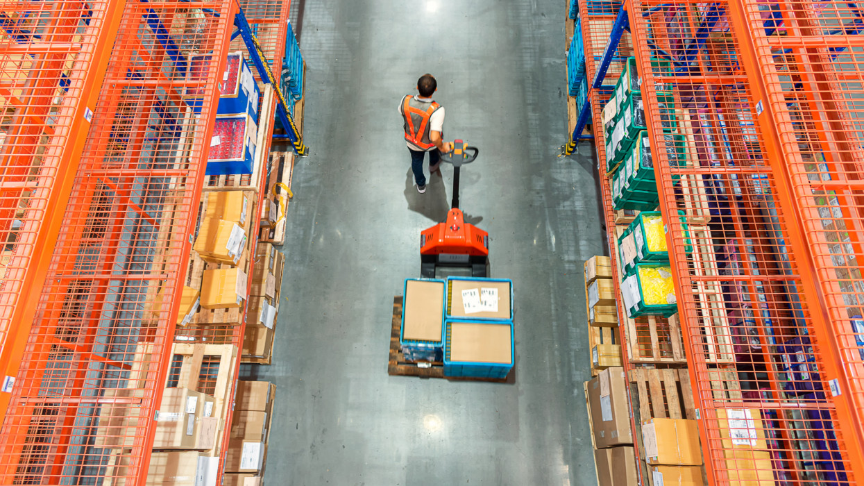 High angle view of Male warehouse worker pulling a pallet truck at distribution warehouse.
