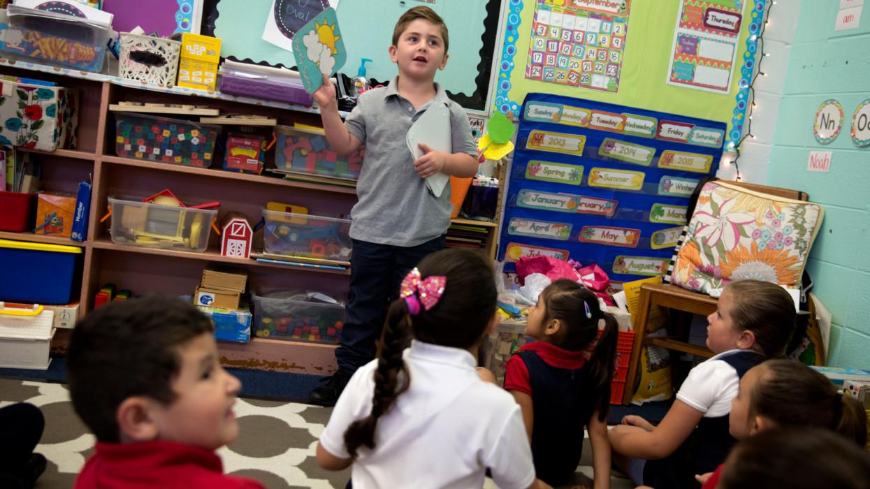 Kindergarten boy talks about the weather in class.