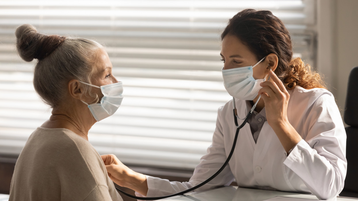 Caring young female doctor in medical facemask hold stethoscope listen to elderly patient heart in hospital. Woman GP or physician do regular checkup examine mature client at consultation in clinic.