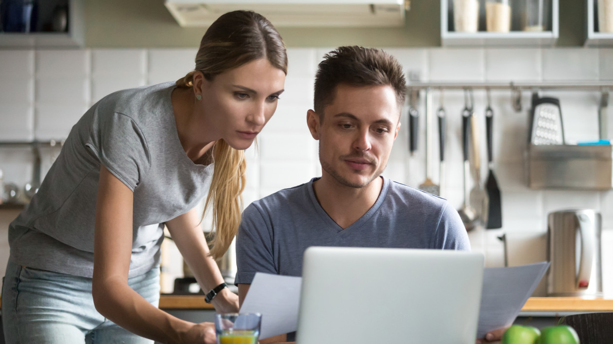 Serious young couple checking papers filling online form on website or holding documents searching information online using laptop banking internet application for calculating paying domestic bills