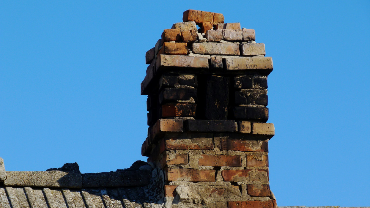 broken and deteriorating grunge old brick meat smoker chimney. cracked mortar joints and loose bricks. clear blue sky. low angle view. weathered concrete tile sloped barn roof. black sooth deposit.