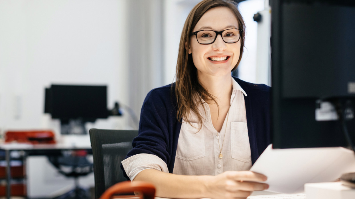 A young businesswoman wearing glasses is sitting in front of a computer in an office room, holding some paper while smiling happily.