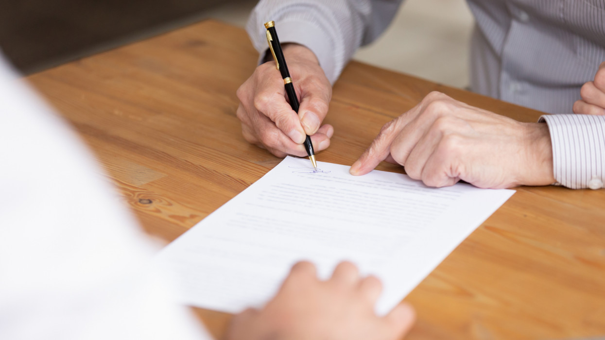Close up elderly businessman hand holding pen put signature on business paper, man signing legal document making investment closing deal, taking bank loan or insurance, writing will testament concept