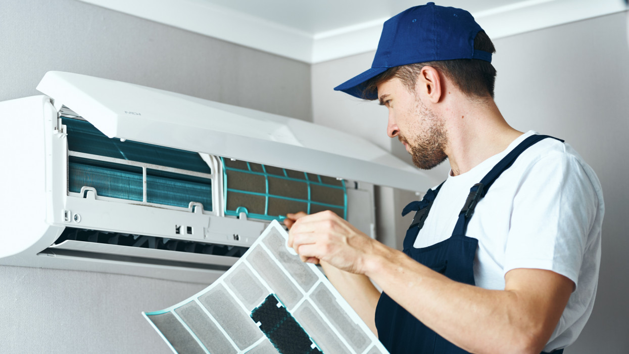 A hired worker repairman cleans and repairs the air conditioner.