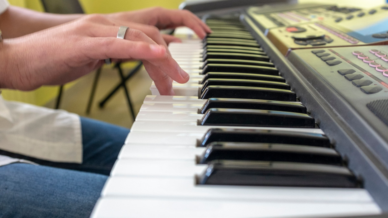 A young man plays a melody on an electronic piano